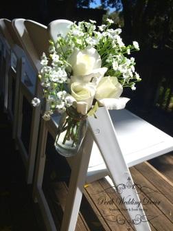 milk jar with silk flowers hanging on aisle chair. $1.50 each
