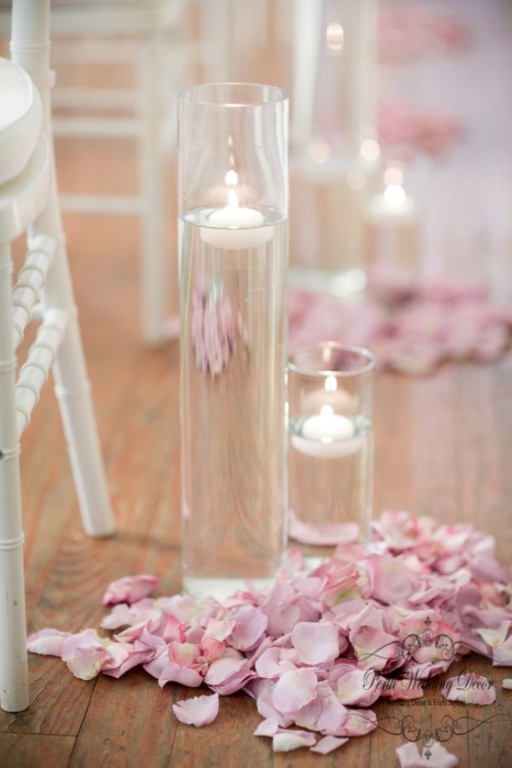Set of 2-3 vases filled with water and floating candle with small ring of petals. $2.50 each