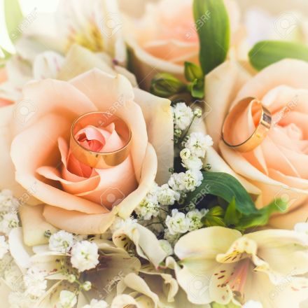 golden rings on wedding bridal bouquet with white, peach and orange roses. Wedding theme